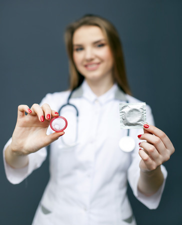 Attractive blurred woman doctor figure with red condom on palm. Conceptual image