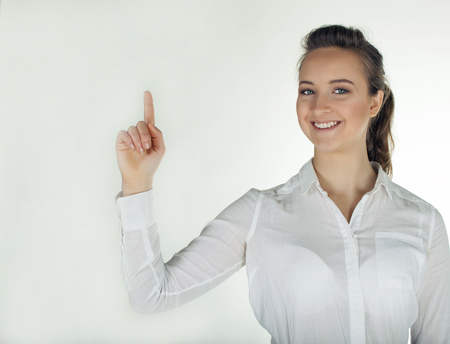 Young business woman holds hand palm up and smile. White background