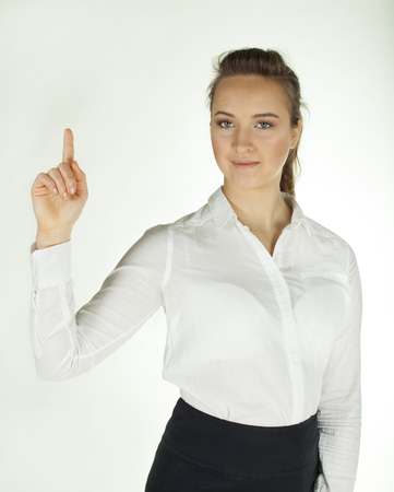 Young woman holds hand palm up and smile. White background Standard-Bild