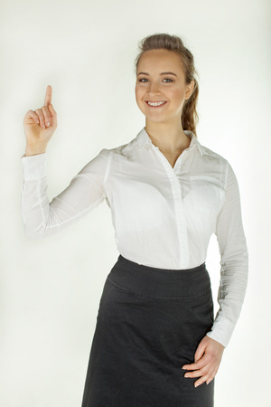 Young smiling woman holds hand palm up. White background Standard-Bild