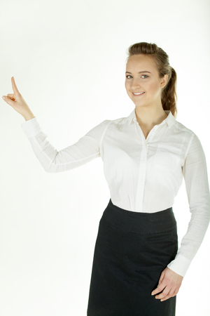 Young business woman holds hand up and smile. White background