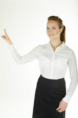 Smiling business woman in office clothes holds finger up.White background