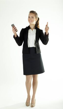 Smiling business woman with smartphone shows finger up .White background