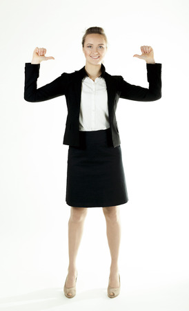 Smiling business woman draws attention, shows finger up .White background