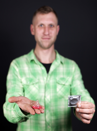 Red condom on palm of man in front of dark background. Close up.