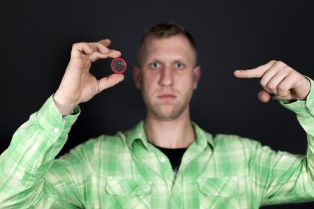 Man show for finger on red condom in front of dark background. Sign OK Standard-Bild