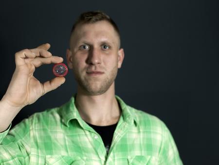 Man show red condom and smile in front of dark background. Standard-Bild