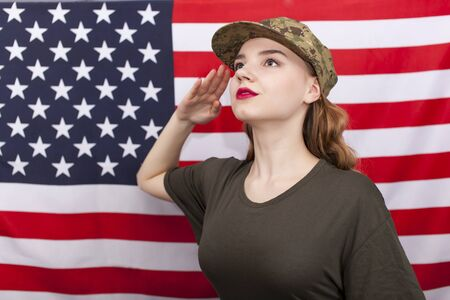 Young attractive woman soldier salute in front of American flag.