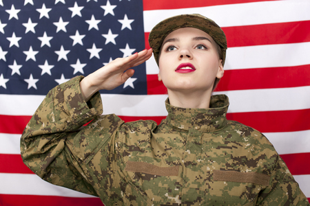 Woman soldier salute in front of American flag.Portrait