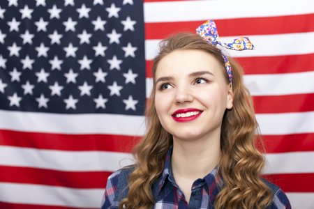 American attractive young woman in front of US flag