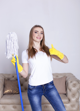 Portrait of happy young woman doing chores cleaning home with floor mop