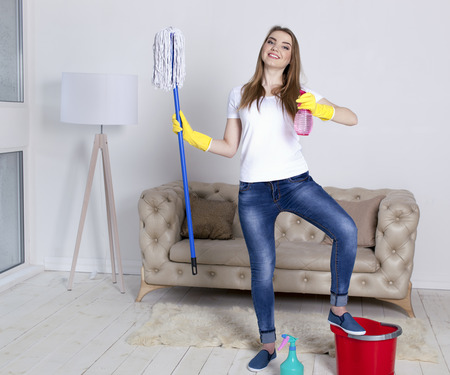 Portrait of happy woman doing chores cleaning home with floor mop and water spray