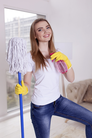 Happy woman with floor mop and water spray smile