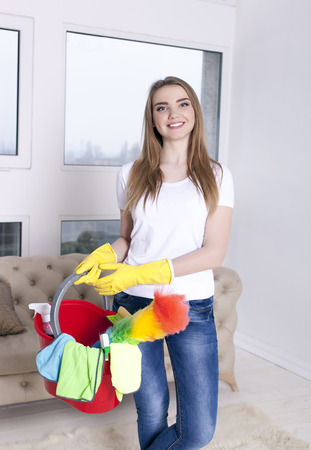 Young woman housewife with bucket in hands and cleaning things