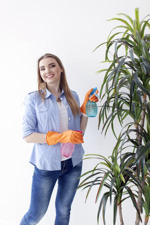 Woman housewife with spray near plant