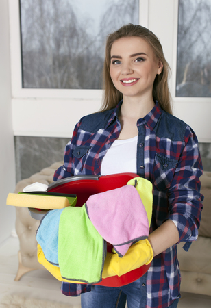 Young smiling woman housewife with bucket, towels. Portrait