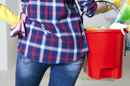 Woman housewife with bucket and towels in hands. Back view close up Standard-Bild