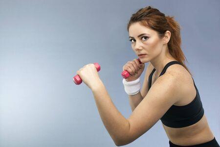 Sport serios girl with red dumbbells looks direct. Portrait Standard-Bild
