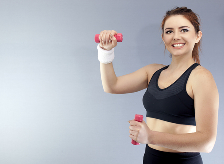 Sport fitness girl with red dumbbells in front of gray background Stock Photo