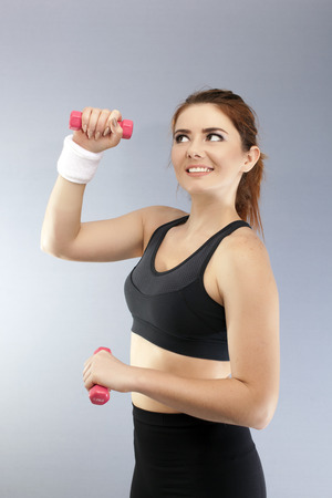 Sport fitness girl with red dumbbells in front of gray background looks up