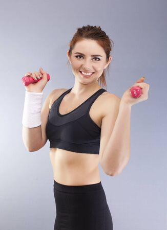 Sport smiling with red dumbbells in front of gray background looks direct
