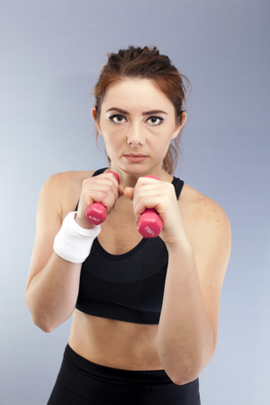 Sport serios girl with red dumbbells boxer pose looks direct. Portrait