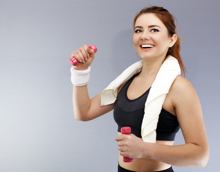 Sport woman with red dumbbells and towel smile. Portrait