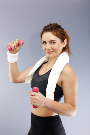 Sport woman with red dumbbells and towel smile, looking in camera.