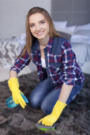 young woman sit on carpet ready to cleaning home and smile Standard-Bild