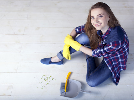 woman sit on floor with scoop for garbage and smile.