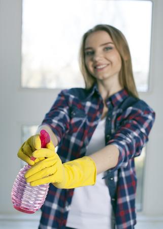 Smiling girl holds detergent bottle in hands. Blurred face