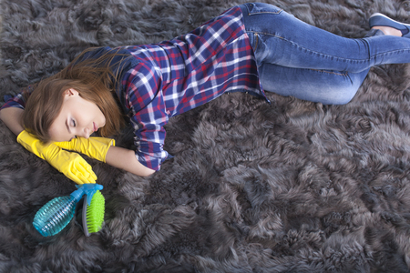 Tired young woman sleeping on carpet after cleaning home