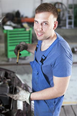 Mechanic examines car oil engine in car repair shop Standard-Bild