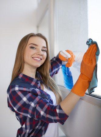 Happy young woman doing cleaning home window and smile