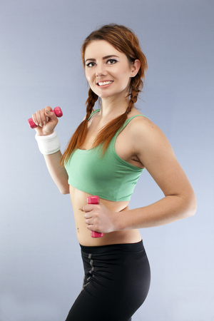 Red dumbbells in hands of smiling fitness woman.