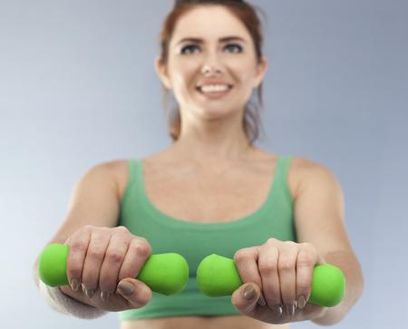 Green dumbbells in hands of woman. Blurred Figure Standard-Bild