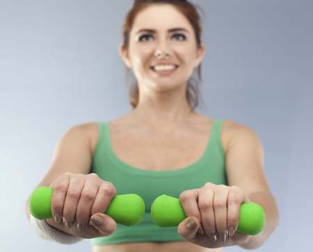 Green dumbbells in hands of woman. Blurred Figure Stock Photo