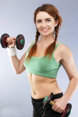 Smiling woman with old dumbbells in looks in camera Stock Photo