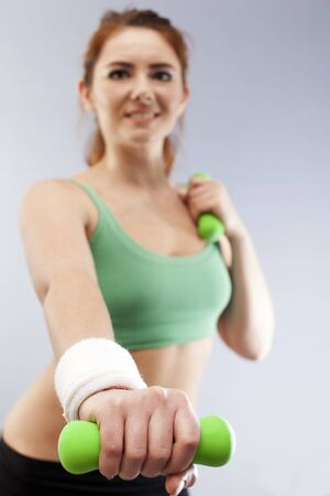 Green dumbbells in hands of fitness young woman. Blurred Figure Standard-Bild