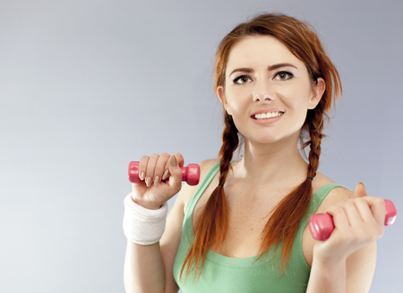 Red dumbbells in hands of smiling fitness woman. Close up Stock Photo