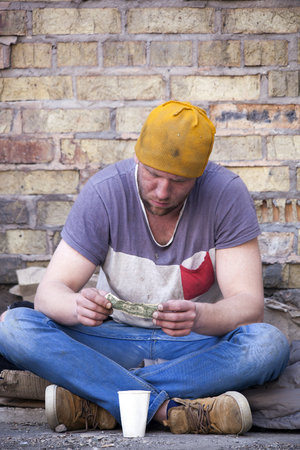 Homeless man with some money sadly sits near wall. No money problem