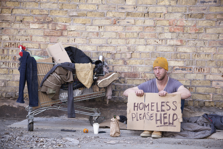 Homeless man with cardboard, sits near wall. Carriage is home