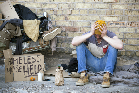 Sad homeless man with cardboard, sits near wall. Carriage is home