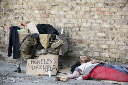 Sad homeless man with cardboard, sleep. Social problem