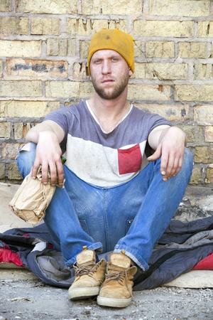 Sad homeless man with alcohol bottle. Social problem