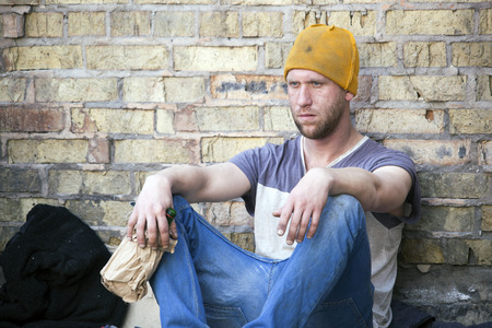 Sad depressed homeless man with alcohol bottle. Social problem