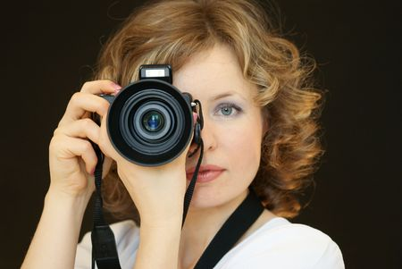 The thoughtful young woman holds a digital camera in a hand photo