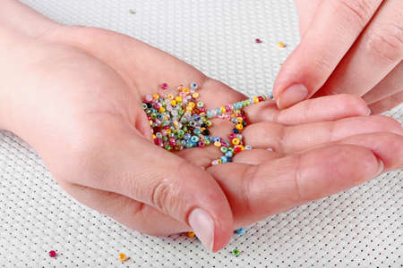 seed beads: The process of embroidery with beads on an outline, a close-up