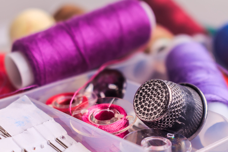 bobbin: sewing accesorries:  thread, bobbin, thimble, needle in plastic box close up with blurred background Stock Photo