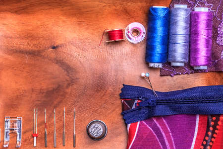 bobbin: sewing accesorries: pin, thimble, thread, bobbin, needle, zip, textile, foot on wooden table Stock Photo